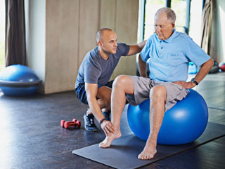 An old man sitting on an exercise receiving physical therapy